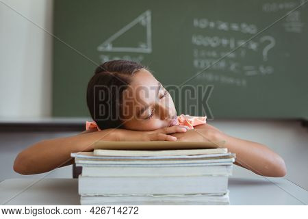 Tired mixed race schoolgirl in classroom sitting at desk sleeping on stack of books. childhood and education at elementary school.