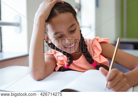 Happy mixed race schoolgirl in classroom sitting at desk smiling and writing in book. childhood and education at elementary school.