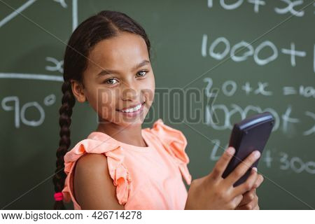 Portrait of smiling mixed race schoolgirl standing at chalkboard in classroom using smartphone. childhood, technology and education at elementary school.