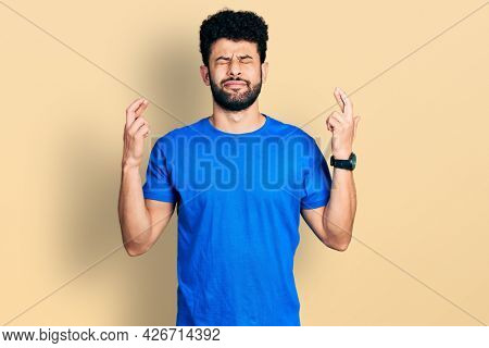 Young arab man with beard wearing casual blue t shirt gesturing finger crossed smiling with hope and eyes closed. luck and superstitious concept.