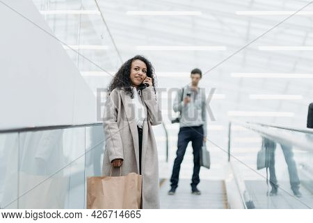 Smiling Woman With Shopping Standing On The Escalator In The Shopping Center .