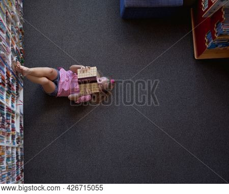 Overhead view of caucasian schoolgirl lying on floor reading book in school library. childhood and education at elementary school.