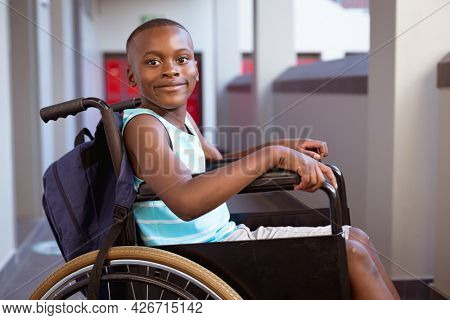 Portrait of smiling disabled african american schoolboy sitting in wheelchair in school corridor. childhood and education at elementary school.