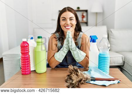 Young brunette woman wearing cleaner apron and gloves cleaning at home praying with hands together asking for forgiveness smiling confident.