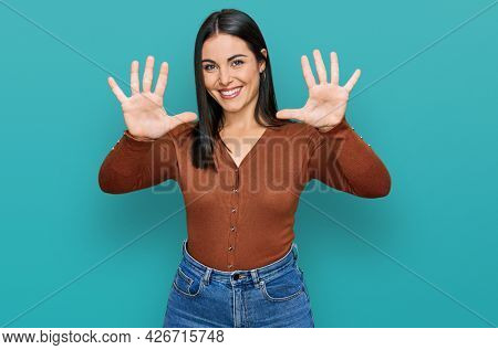 Young hispanic woman wearing casual clothes showing and pointing up with fingers number ten while smiling confident and happy.