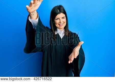 Young hispanic woman wearing judge uniform looking at the camera smiling with open arms for hug. cheerful expression embracing happiness.