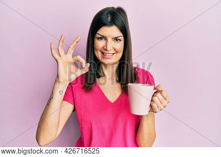 Young hispanic woman drinking a cup of coffee annoyed and frustrated shouting with anger, yelling crazy with anger and hand raised