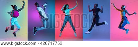 Group Of People, Young Joyful Women And Men Jumping Isolated Over Multicolored Neon Backgrounds.