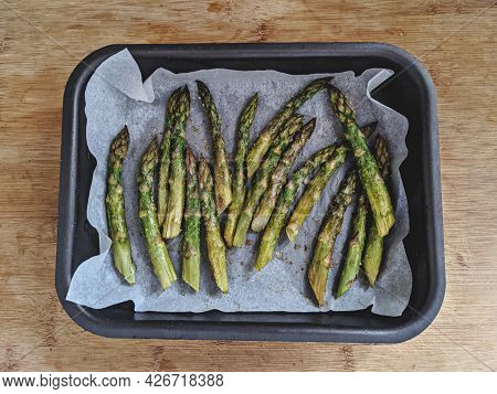 Baked Asparagus In Baking Dish Cooking In Oven On Wooden Surface Table, Healthy Eating And Delicious
