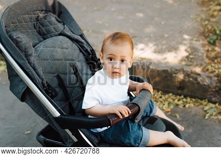 Portrait Of A Funny Little Child Sitting In A Stroller And Looking At The Camera, Outdoors. Kid In A