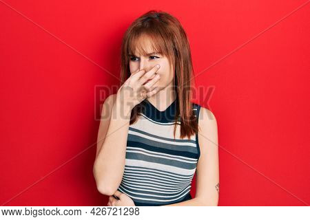 Redhead young woman wearing casual t shirt smelling something stinky and disgusting, intolerable smell, holding breath with fingers on nose. bad smell