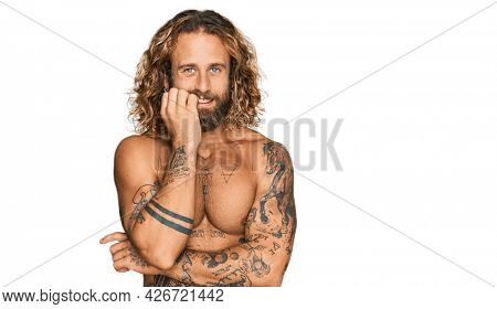 Handsome man with beard and long hair standing shirtless showing tattoos looking stressed and nervous with hands on mouth biting nails. anxiety problem.