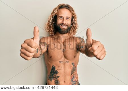 Handsome man with beard and long hair standing shirtless showing tattoos approving doing positive gesture with hand, thumbs up smiling and happy for success. winner gesture.