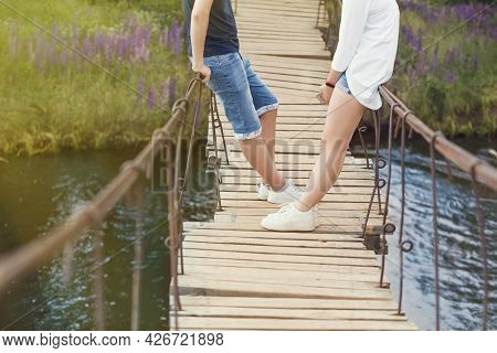 Two People On A Hanging Staggering Bridge Are Talking , Figuring Out, Sorting Things Out A Relations
