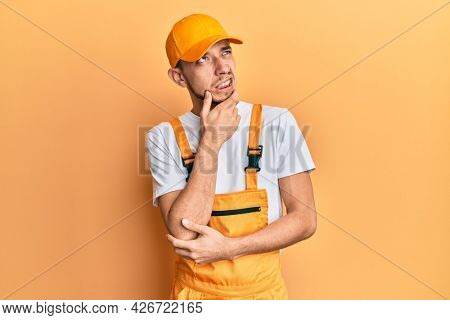 Hispanic young man wearing handyman uniform thinking worried about a question, concerned and nervous with hand on chin