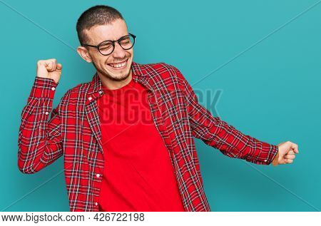 Hispanic young man wearing casual clothes dancing happy and cheerful, smiling moving casual and confident listening to music