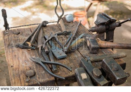 Blacksmith Tools And Instruments On Wooden Workbench, Table At Outdoor Forge, Workshop - Close Up. H