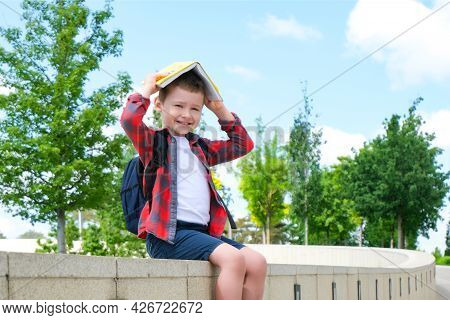A Schoolboy With A Book On His Head Is Like A Roof On The Street On The Way To School. Back To Schoo