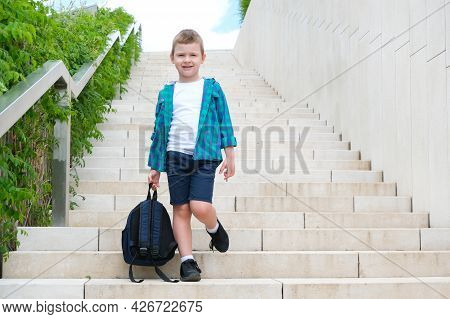 Schoolboy With A Backpack In His Hand On The Street On The Way To School Goes Down The Stairs. Back