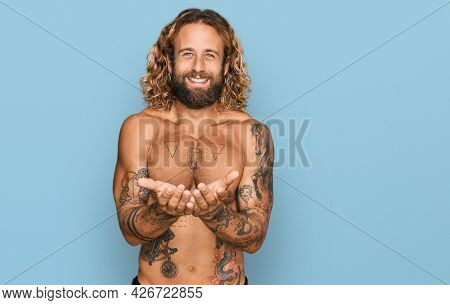 Handsome man with beard and long hair standing shirtless showing tattoos smiling with hands palms together receiving or giving gesture. hold and protection