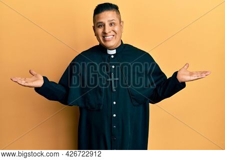 Young latin priest man standing over yellow background smiling showing both hands open palms, presenting and advertising comparison and balance