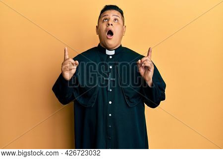 Young latin priest man standing over yellow background amazed and surprised looking up and pointing with fingers and raised arms.