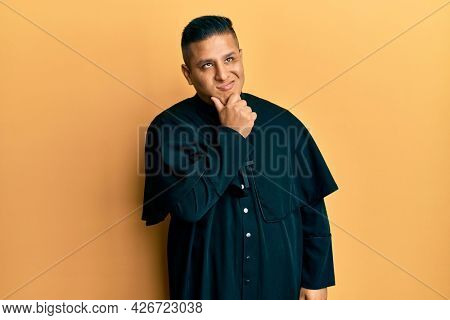 Young latin priest man standing over yellow background thinking worried about a question, concerned and nervous with hand on chin