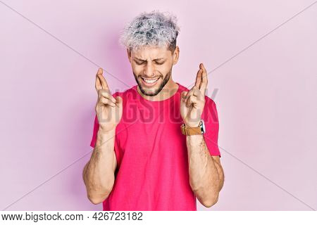 Young hispanic man with modern dyed hair wearing casual pink t shirt gesturing finger crossed smiling with hope and eyes closed. luck and superstitious concept.