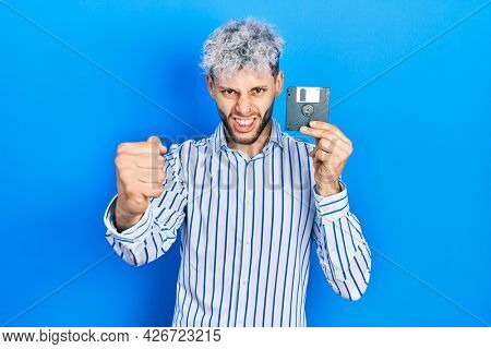 Young hispanic man with modern dyed hair holding floppy disk annoyed and frustrated shouting with anger, yelling crazy with anger and hand raised