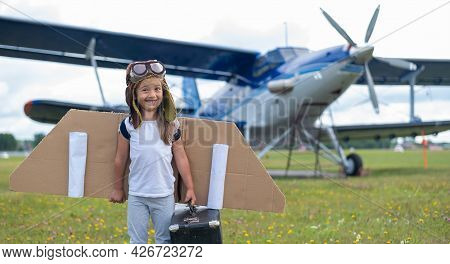 A Little Girl In A Pilots Costume Holds A Retro Suitcase In The Field Near The Plane With A Propelle