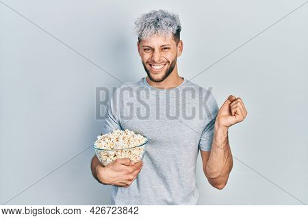 Young hispanic man with modern dyed hair eating popcorn screaming proud, celebrating victory and success very excited with raised arm