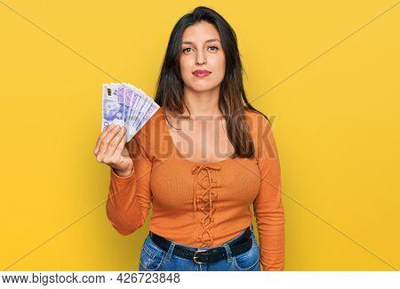Beautiful hispanic woman holding 20 swedish krona banknotes thinking attitude and sober expression looking self confident