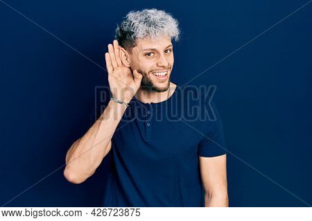 Young hispanic man with modern dyed hair wearing casual blue t shirt smiling with hand over ear listening and hearing to rumor or gossip. deafness concept.