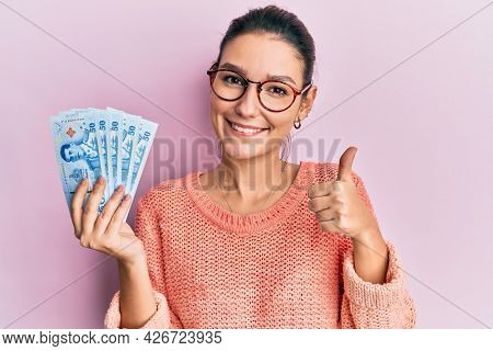 Young caucasian woman holding 50 thai baht banknotes smiling happy and positive, thumb up doing excellent and approval sign