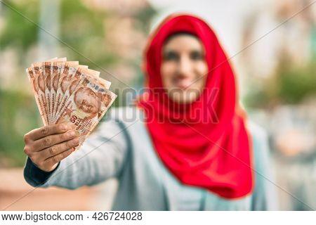 Young arab woman wearing hijab holding turkish lira banknotes at the city.