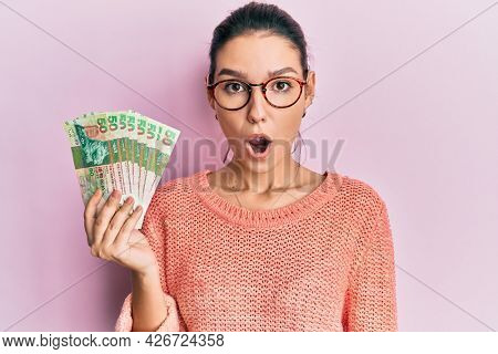 Young caucasian woman holding hong kong dollars banknotes scared and amazed with open mouth for surprise, disbelief face