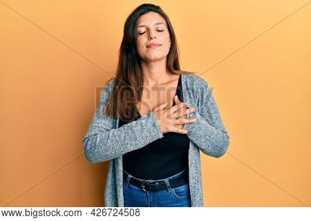 Beautiful hispanic woman wearing casual clothes smiling with hands on chest, eyes closed with grateful gesture on face. health concept.