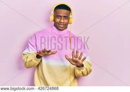 Young black man listening to music wearing headphones disgusted expression, displeased and fearful doing disgust face because aversion reaction. with hands raised