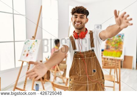Young hispanic man at art studio looking at the camera smiling with open arms for hug. cheerful expression embracing happiness.