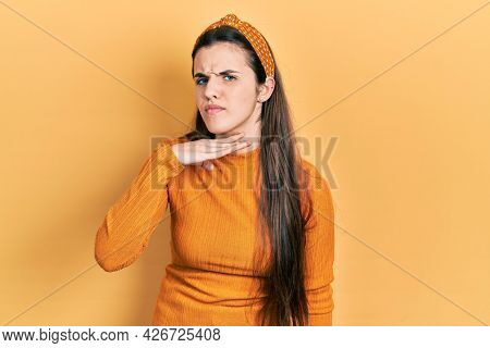 Young brunette teenager wearing casual yellow sweater cutting throat with hand as knife, threaten aggression with furious violence