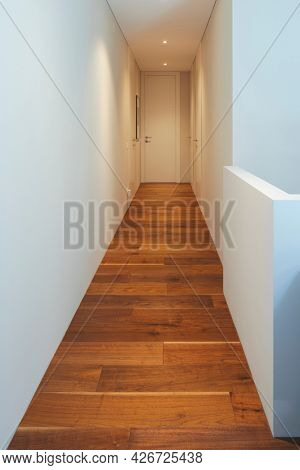 White hallway with spotlights in a stylish modern home. White walls, perfect for text. Nobody inside