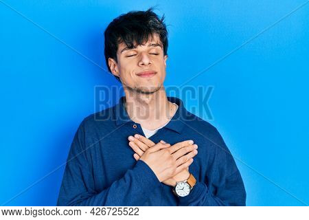 Handsome hipster young man stranding over blue background smiling with hands on chest with closed eyes and grateful gesture on face. health concept.