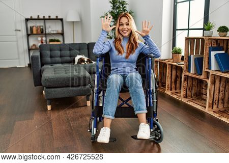 Young beautiful woman sitting on wheelchair at home showing and pointing up with fingers number ten while smiling confident and happy.