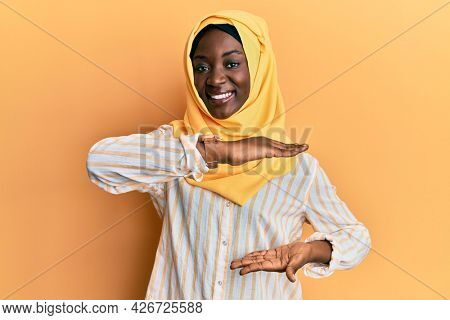 Beautiful african young woman wearing traditional islamic hijab scarf gesturing with hands showing big and large size sign, measure symbol. smiling looking at the camera. measuring concept.
