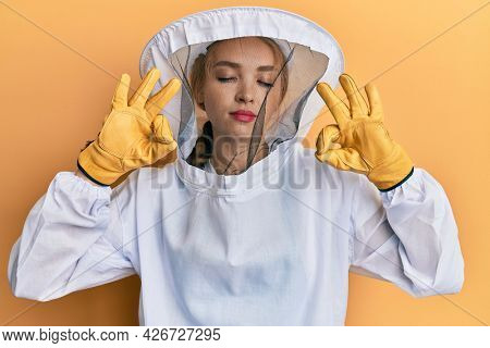 Beautiful blonde caucasian woman wearing protective beekeeper uniform relax and smiling with eyes closed doing meditation gesture with fingers. yoga concept.