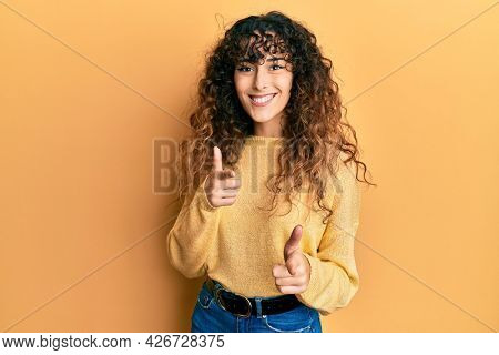Young hispanic girl wearing casual clothes pointing fingers to camera with happy and funny face. good energy and vibes.