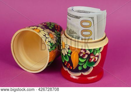 Plundering Of State Budget, Corruption Concept. Russian Matryoshka Full Of Money. Rolled Hundred-dol