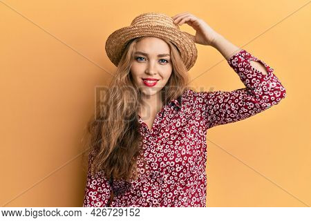 Beautiful blonde caucasian woman wearing summer hat confuse and wonder about question. uncertain with doubt, thinking with hand on head. pensive concept.