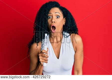 Middle age african american woman holding electric toothbrush scared and amazed with open mouth for surprise, disbelief face