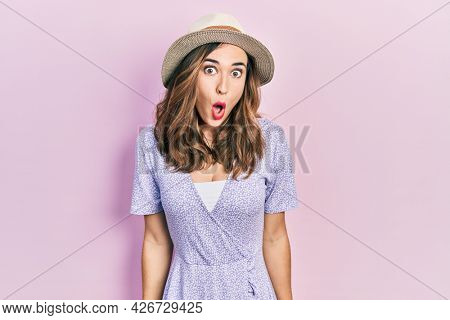 Young hispanic girl wearing summer hat scared and amazed with open mouth for surprise, disbelief face